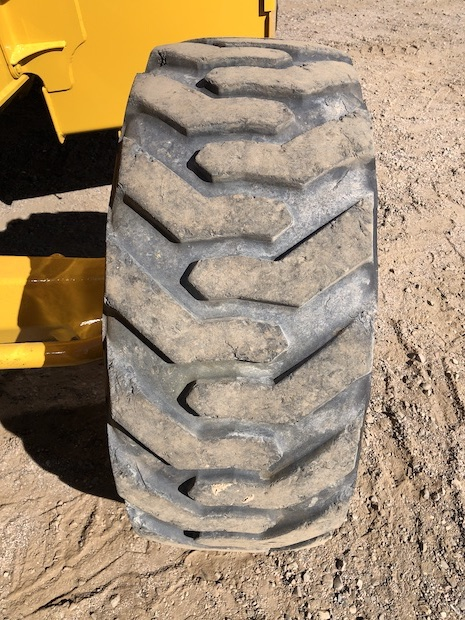 2013 John Deere 310K EP with Extend-a-hoe. Drivers side front tire.